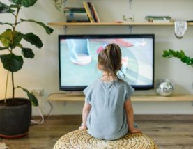 faceless girl watching tv on wicker stool at home